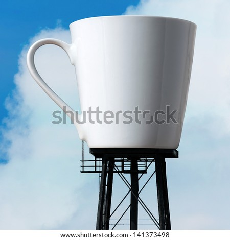 An enormous supply of coffee in the form of a coffee mug atop water tower stilts.  A funny concept for caffeine addiction or coffee / tea lovers. - stock photo