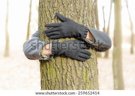 An environmentalist is embracing a tree to demonstrate is love for nature and environment. - stock photo