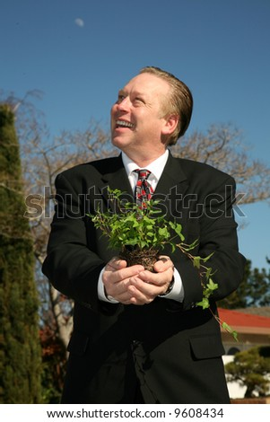 an environmentally friendly business man in a nice suit holds a green plant to save the earth from Global Warming - stock photo