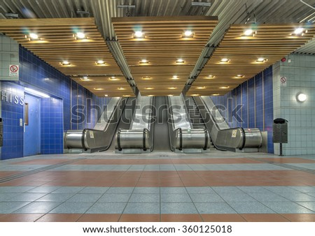An escalator down to a tram station. - stock photo