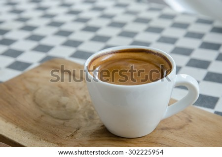 an Espresso coffee in a white cup on the table. - stock photo