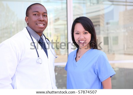An ethnic happy medical man and woman team outside hospital