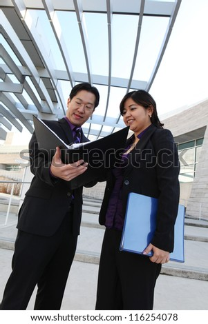 An ethnic man and woman business team looking at notebook - stock photo