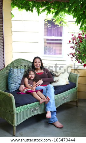 An ethnic mother and daughter snuggle on a wicker couch on a porch on a sunny day. - stock photo