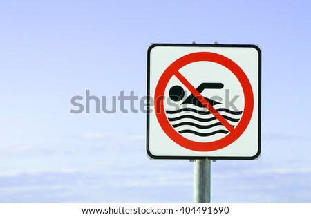 An European warning sign at the beach with man swim and not symbol, Caution No Swimming allowed - stock photo