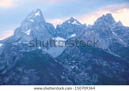 An evening sunset view of the Grand Teton Mountains with the Teton Glacier visible in summer. Grand Teton National Park, Wyoming, United States. - stock photo