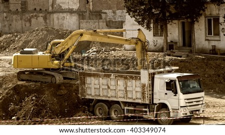 An excavator and a big truck are operating in a busy construction site - stock photo
