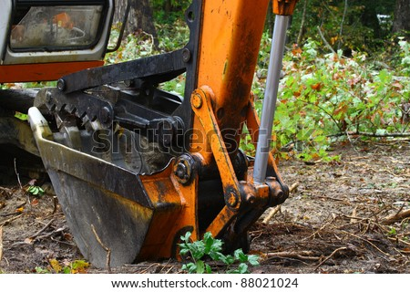 An Excavator bucket with the jaw attachment on it used for lifting trees and debris resting on the ground outside in the woods with room for your text. - stock photo