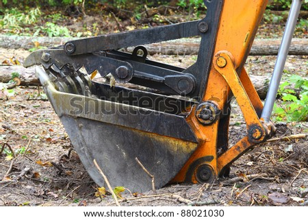An Excavator bucket with the jaw attachment on it used for lifting trees and debris resting on the ground outside in the woods. - stock photo