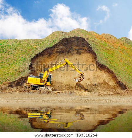 An excavator in old mine. Damaged landscape before recultivation. - stock photo