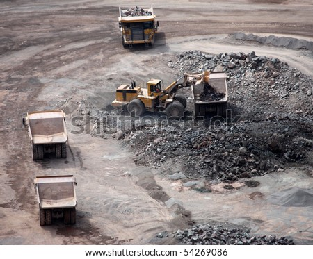An Excavator Loading Lorries in a Granite Quarry. - stock photo