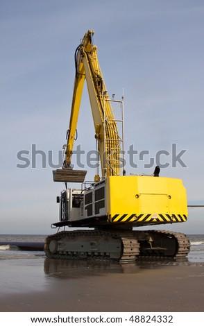 An Excavator on the beach of Scheveningen NL - stock photo