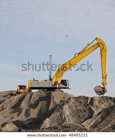 an Excavator on the beach on a dredging project in holland - stock photo