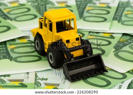 an excavator standing on euro banknotes. symbol photo for costs, revenues and subsidies in the construction industry and the construction industry - stock photo
