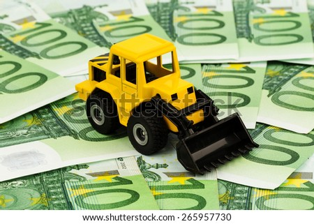 an excavator stands on euro banknotes. symbolic photo for cost, revenue and grants in the construction industry and the construction industry - stock photo