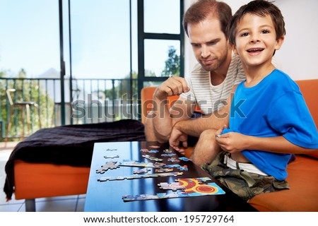 An excited little boy looking up at the camera while doing a puzzle with his father - stock photo