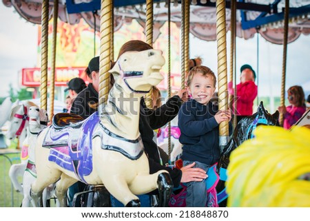 An excited young boy sits on a horse on a carousel as the ride starts in an amusement park.  - stock photo