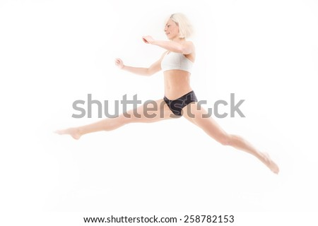 An excited young sportswoman leaping for joy while isolated on a white background