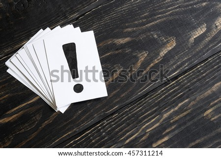 An exclamation mark on table concept for confusion, question or solution on wooden background on the left - stock photo