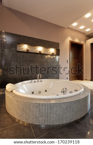 An exclusive round bath with small tiles in an elegant bathroom - stock photo