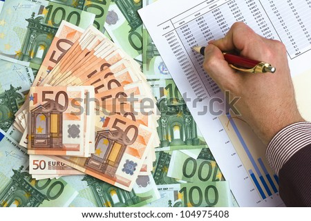an executive reviews the accounting benefits across many euro banknotes - stock photo