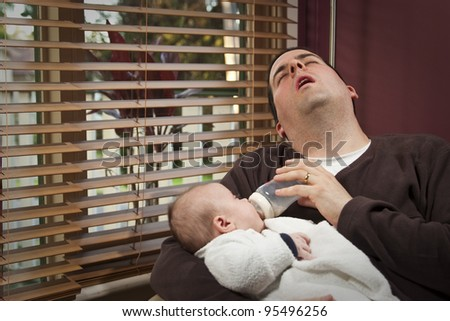 An exhausted father feeds young child in the morning - stock photo