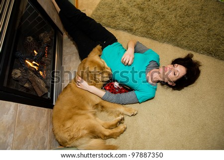 An exhausted woman sleeping comfortably next to a fire with her Golden Retriever dog. - stock photo