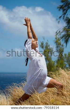 An exotic Hawaiian woman in a flowing white dress does a yoga pose in the tall grass overlooking the ocean on Maui, Hawaii. Vertical image orientation. - stock photo