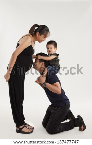 An expecting mother playing with her son carried by father