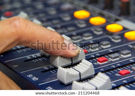 An expert adjusting audio mixing console.select focus - stock photo