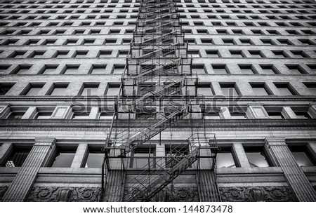 An exterior fire escape on the side of a turn-of-the-century brick building.  Black and white. - stock photo