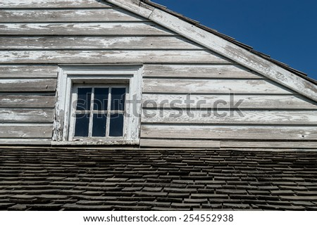 An exterior of a historic home with peeling paint on wooden siding. - stock photo