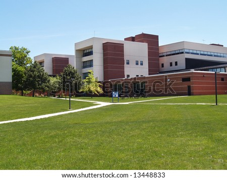 an exterior view of a college building with a large grass area in front of it - stock photo