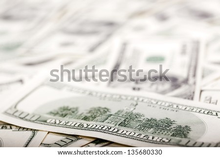 An extreme close up of the reverse side of a 100 US$ money note, with very shallow depth of field. Defocused in the background there's a very large amount of identical bills. - stock photo