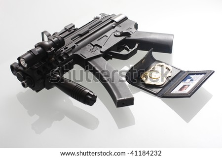 An FBI badge and assault gun on a table.