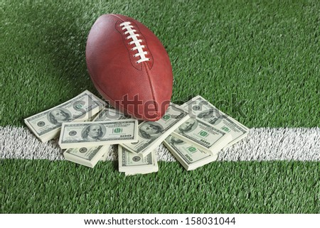 An football sits with a pile of money on a green field - stock photo