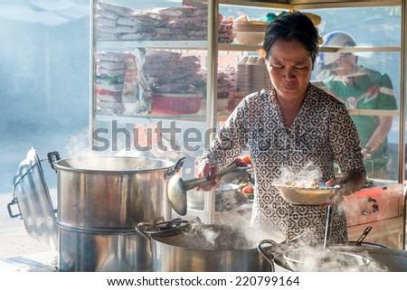 AN GIANG, VIET NAM- 20 SEPT 2014: Chef preparing noodle soup to bowl: noodle, pork, sauce to serve breakfast for customers in the early morning. Vietnamese often use this kind of food for breakfast. - stock photo