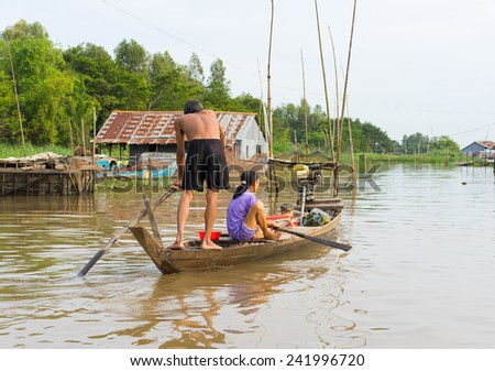 An Giang, Vietnam - Nov 29, 2014: A family moving by rowing boat, the most common transportation mean of rural people in Mekong delta, southern Vietnam - stock photo