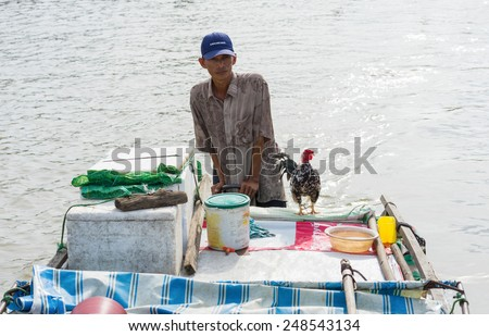 An Giang, Vietnam - Nov 30, 2014: A man with his cock on motorboat in river of Mekong delta. The cock is for selling to someone who interest in buying him - stock photo