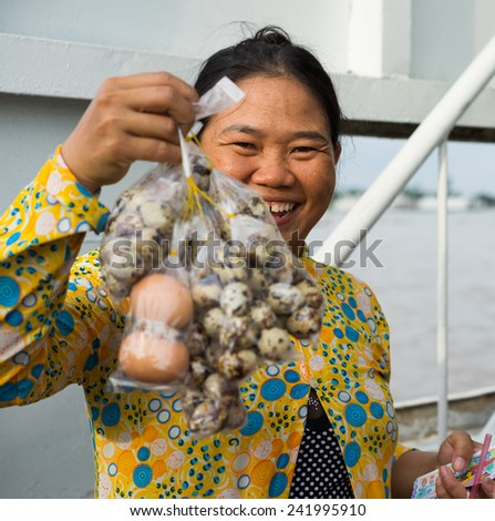 An Giang, Vietnam - Nov 29, 2014: Close-up shot of a rural woman selling boiled quail egg on passenger ferry in Tien river, Mekong delta - stock photo
