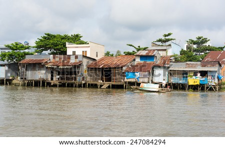An Giang, Vietnam - Nov 30, 2014: Houses of local people staying along river in Mekong delta, southern Vietnam - stock photo