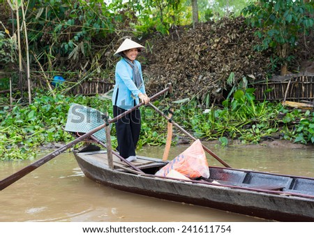 An Giang, Vietnam - Nov 29, 2014: Rural woman rows tourism boat in Tien river, Mekong delta, southern Vietnam. There are more and more tourists come to Mekong delta to enjoy the living in rivers - stock photo