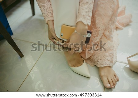 An Giang, Vietnam - September 30th, 2016: closeup of brides are wearing shoes with white wedding gown in the locker room