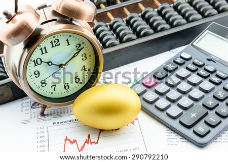 An golden egg with a clock, a calculator and an abacus on business and financial summary reports. A long term sustainable growth investment concept. - stock photo