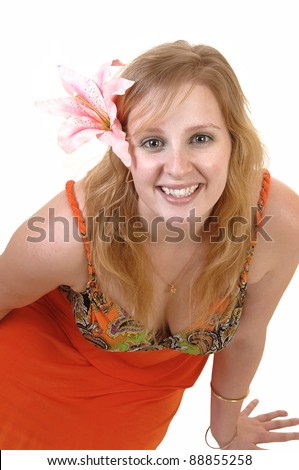 An gorgeous teenager girl in a colorful orange dress and a lily in her hair standing in the studio with a pretty smile, for white background.