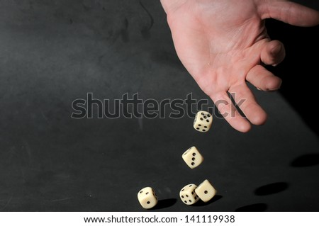 An Hand Play Dice on a Dark Background