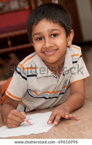 an handsome indian kid doing homework - stock photo