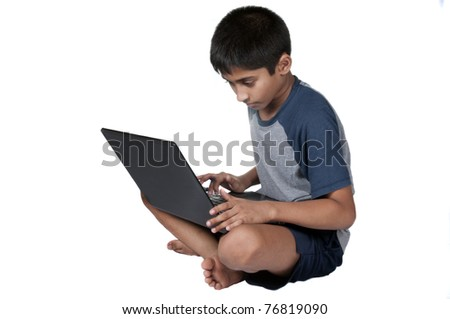 An handsome Indian kid having fun with laptop - stock photo