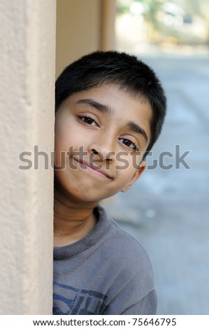 An handsome Indian kid looking shy at a local park - stock photo