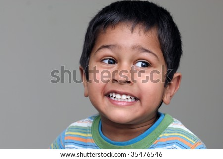 An handsome Indian kid looking very animated - stock photo